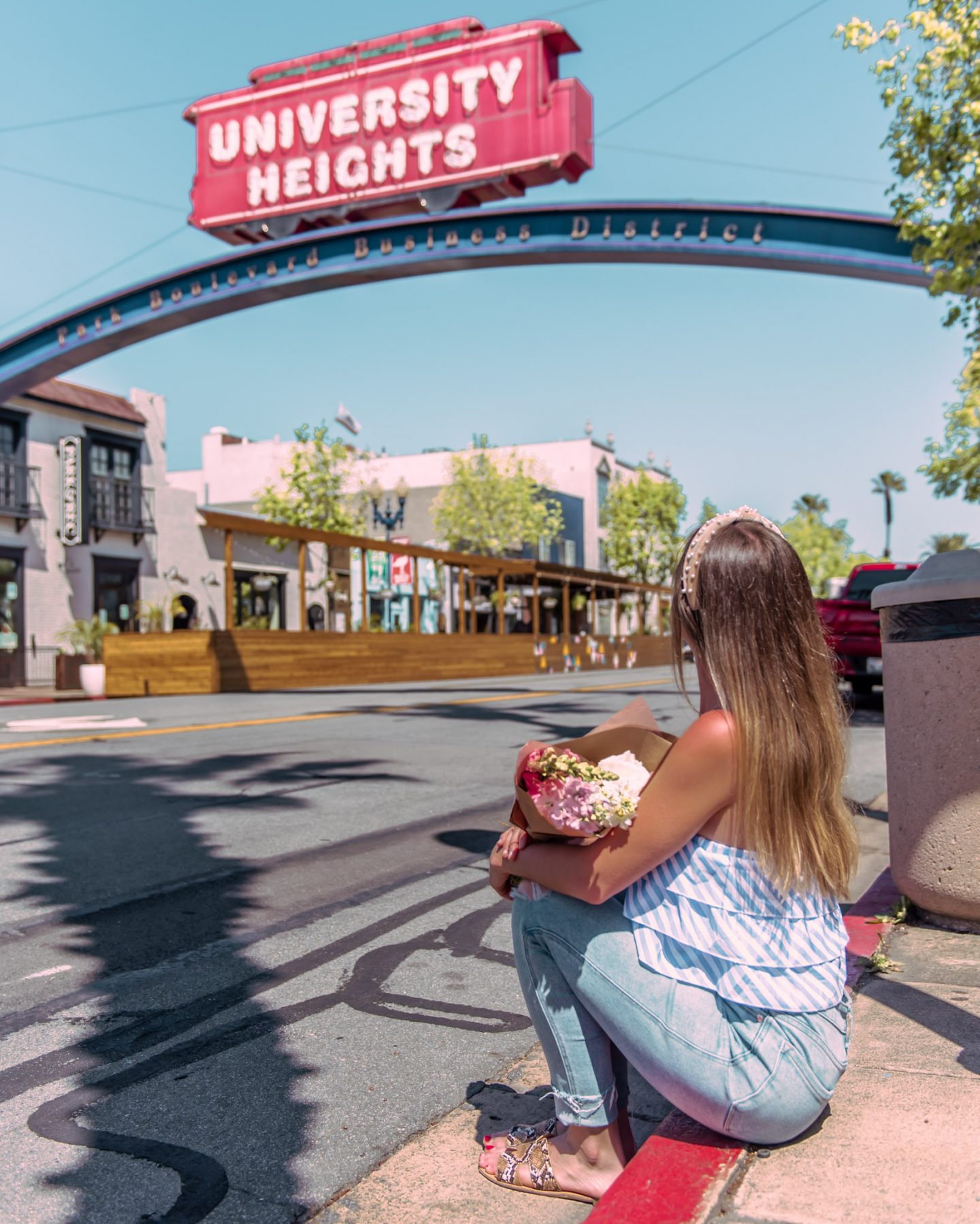 Sitting under the university heights street sign in San diego california